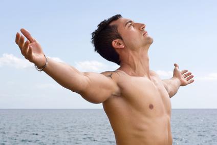 Modelo masculino con los brazos abiertos hacia el cielo