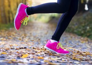 Close up of runner's feet running in autumn leaves training exercise